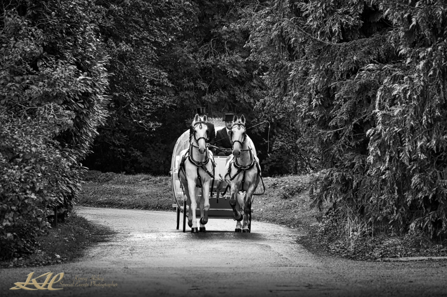 Fairytale wedding carriage approaching Hever Castle with Bride