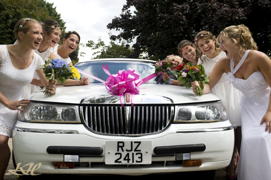 Bride and bridesmaids posing by white limousine