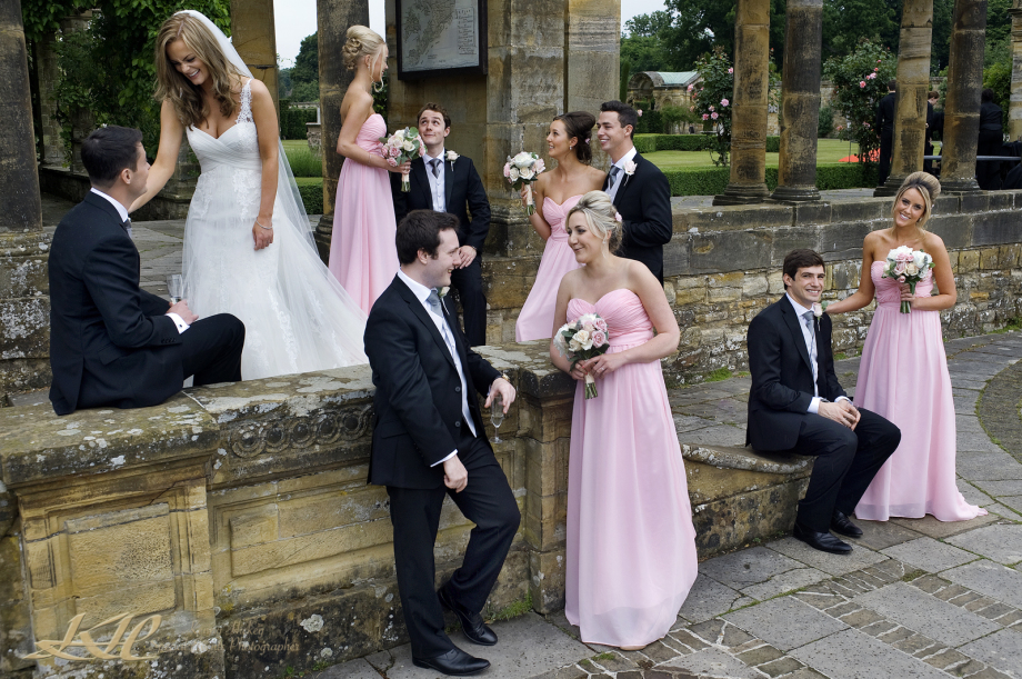 contemporary shot of bride & groom and all bridal party at Hever castle