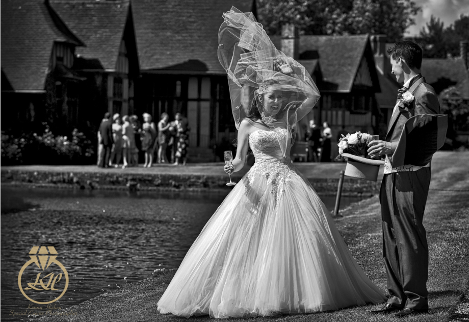 Brides veil blows up in front of smiling groom at Hever Castle