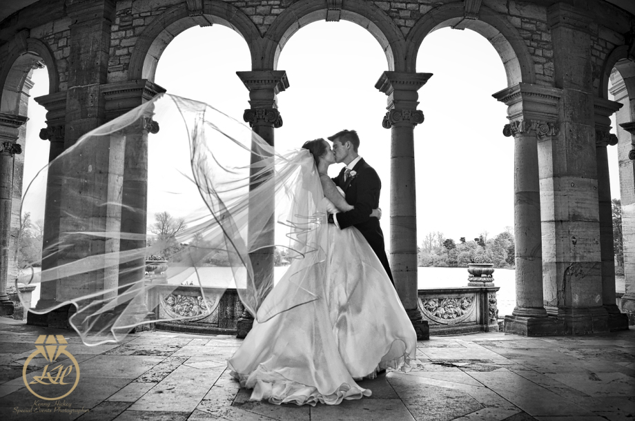 Bride & Groom on Hever castle Loggia kissing with blowing veil