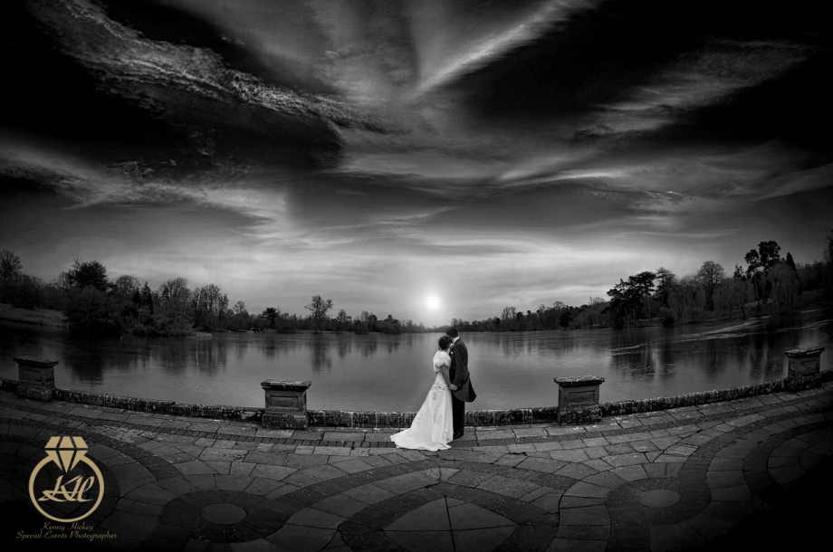 Bride & Groom romantic cuddle by never castle lake at sunset