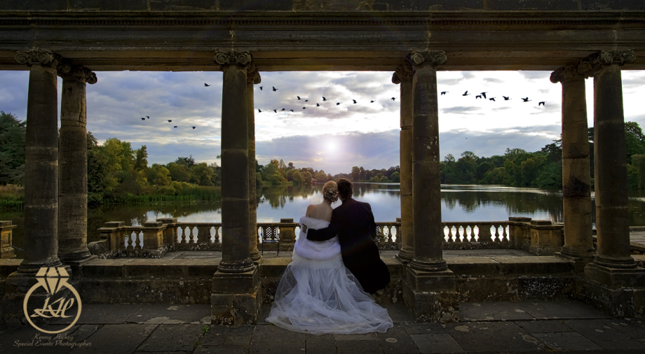 Bride & Groom sitting on the Loggia at Hever castle lake with birds flying by