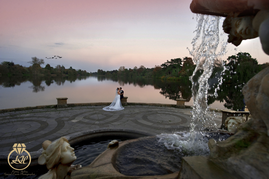 Bride & Groom romantic cuddle by Hever Castle Lake and water fountain at sunset, red sky