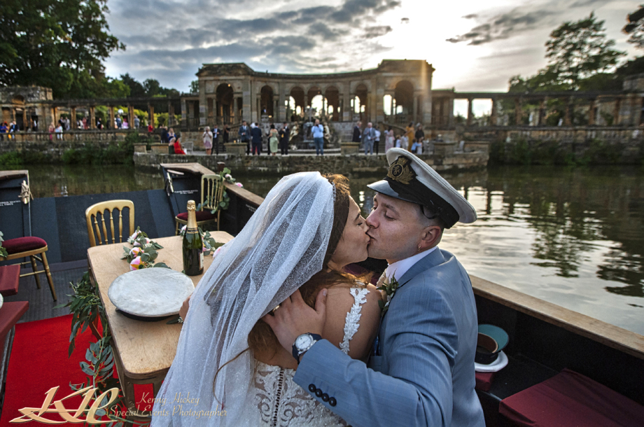 bride and groom kissing on boat in lake at Hever Castle in sailor hat