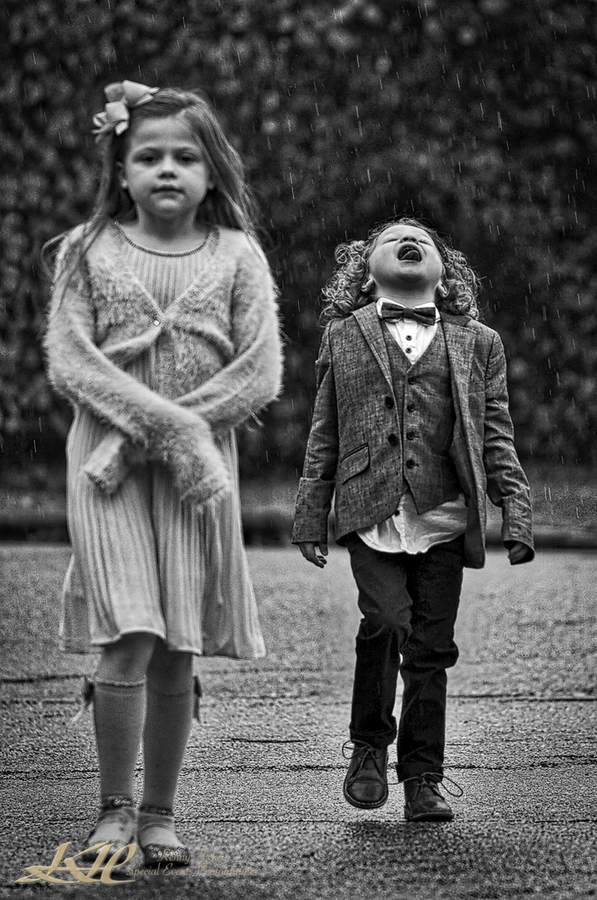 Young boy wedding guest catching rain in his mouth