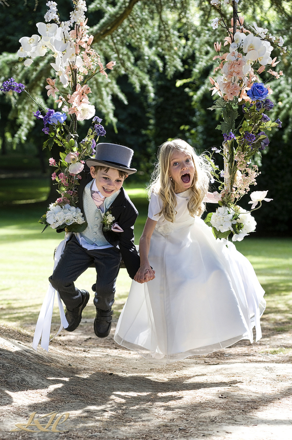 Bridesmaid & Page Boy laughing on flowered swing