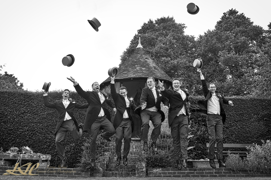 Groom & Groomsmen jumping throwing their hats into the air