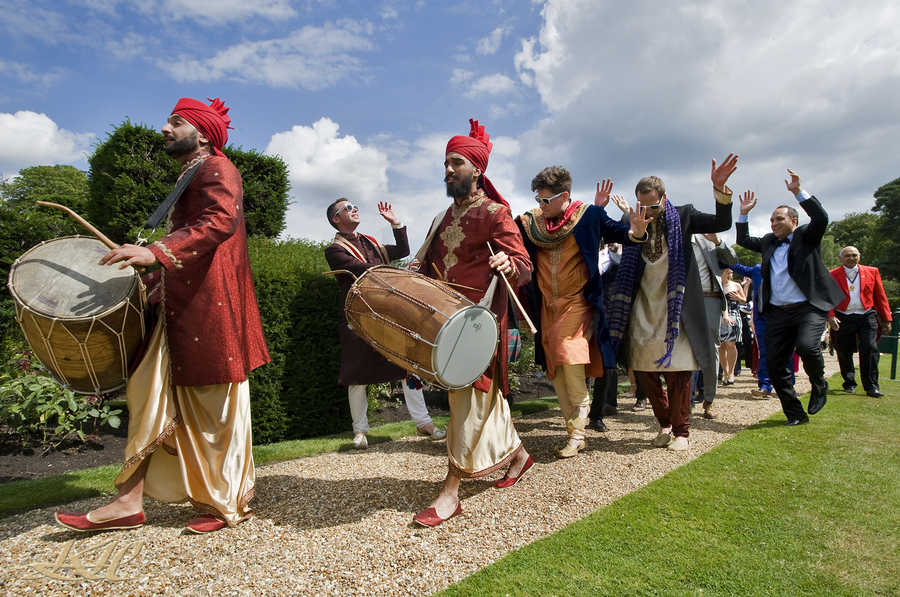 Indian wedding party dancing to drums outside Hever Castle