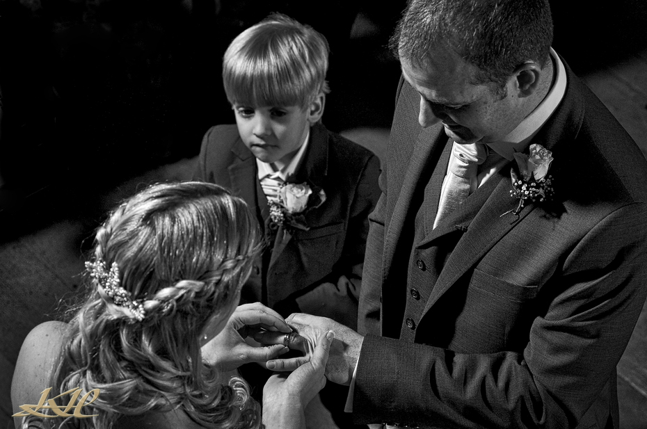 Bride putting ring on Groom in church service