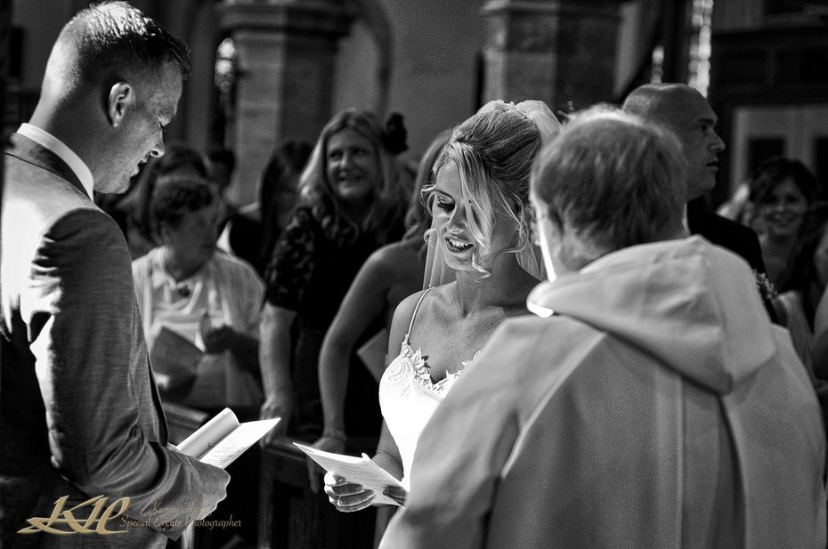 Bride & Groom sing at church service in black & white, Kent Wedding Photographer