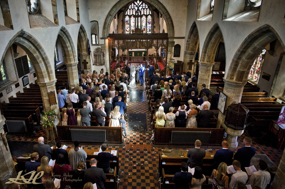 view of church ceremony from balcony in colour, Kent wedding photographer