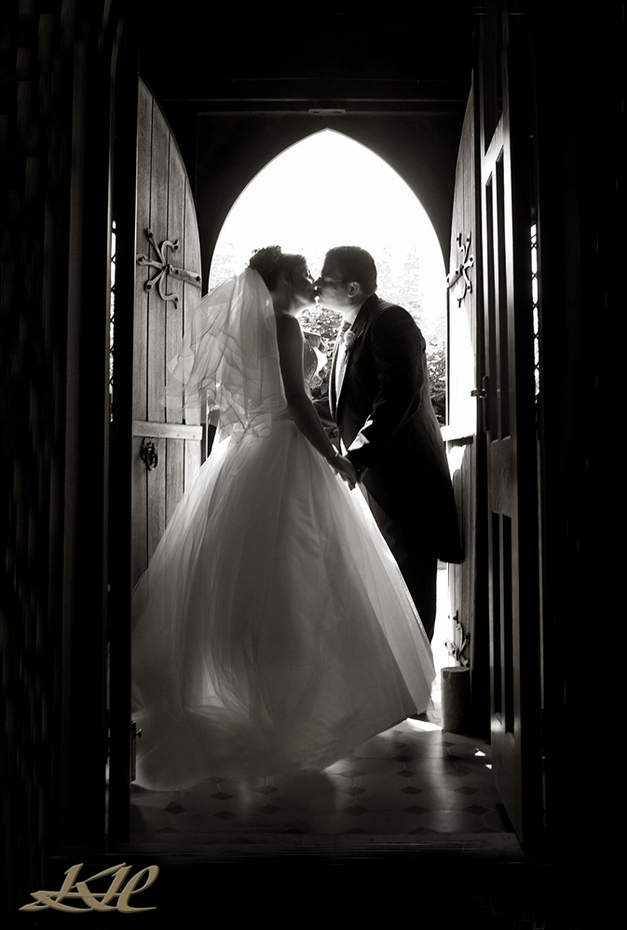 Bride & Groom kissing in church entrance
