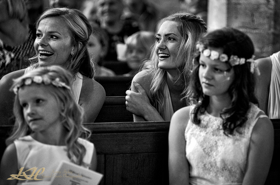 smiling bridesmaids at church service in black & white