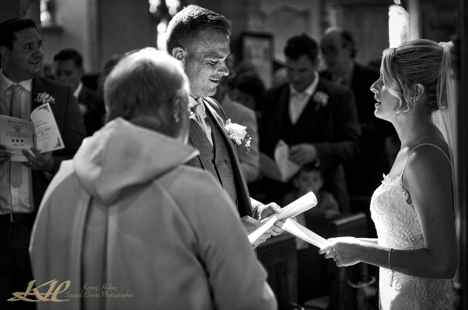 Bride & Groom during vows and singing church service in black & white, Kent wedding photographer