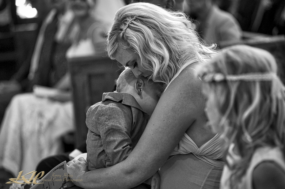 Bridesmaid cuddling sleeping child during church service in black & white