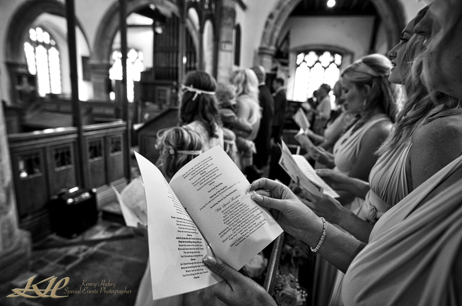 Bridesmaids singing with order of service in church in black & white, Kent wedding photographer