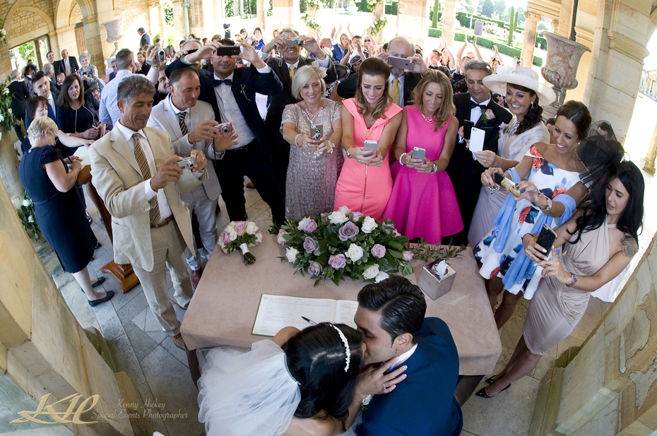 Bride & Groom kissing with lots of guest photographing them at ceremony Hever Castle Loggia