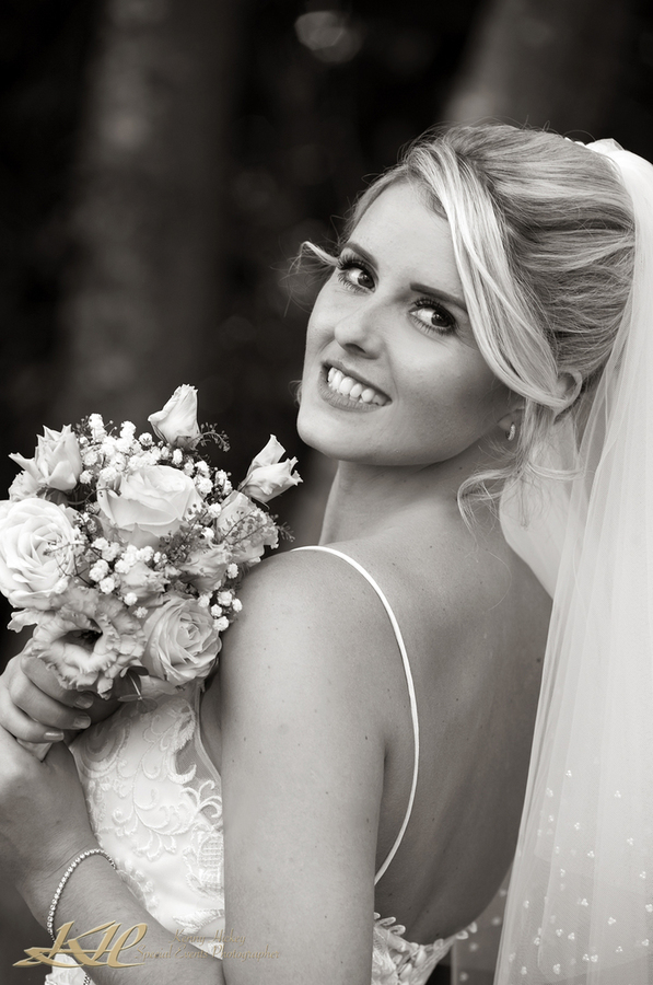 Beautiful Bride looking back with bouquet in black & white, Kenny Hickey Photography, Kent Wedding Photographer