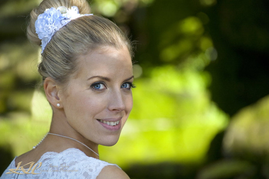 pretty bride with hair up against green background Hever Castle