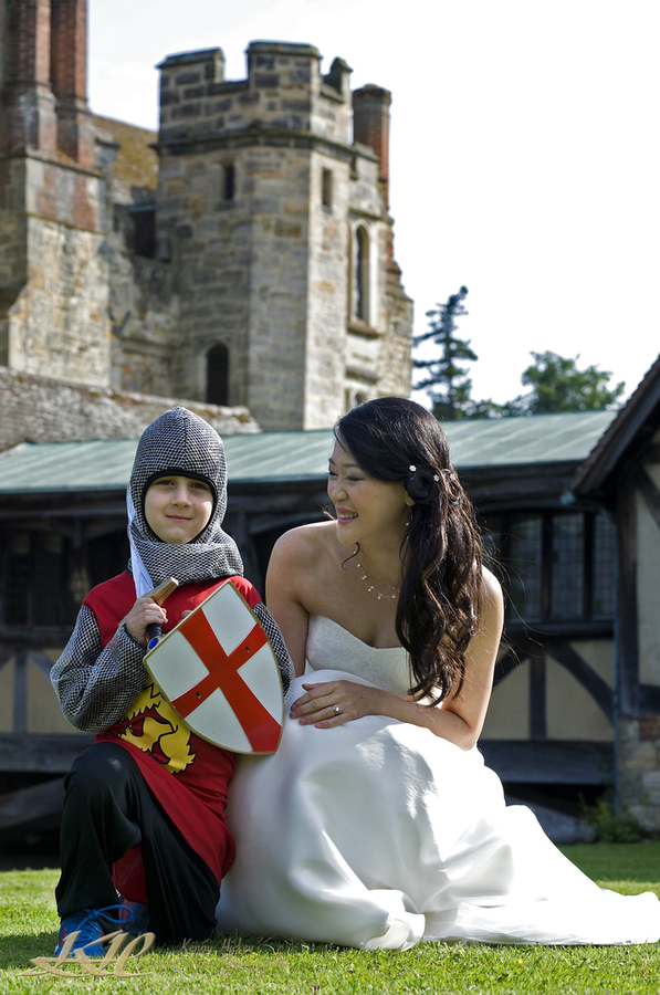 Bride at Hever Castle with boy in knights outfit with sword