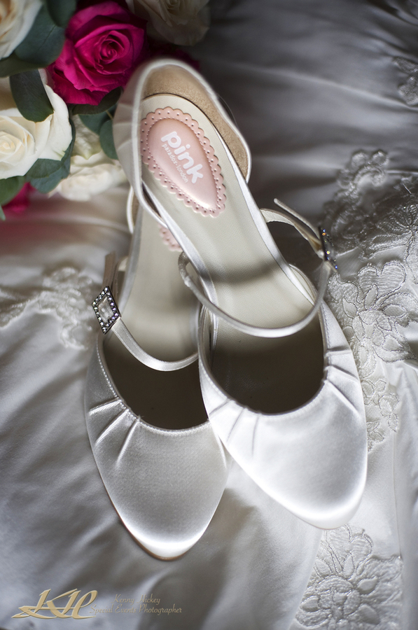brides shoes on wedding dress with flowers