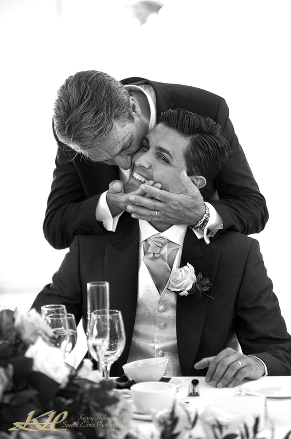Father kissing groom in black & white wedding reception