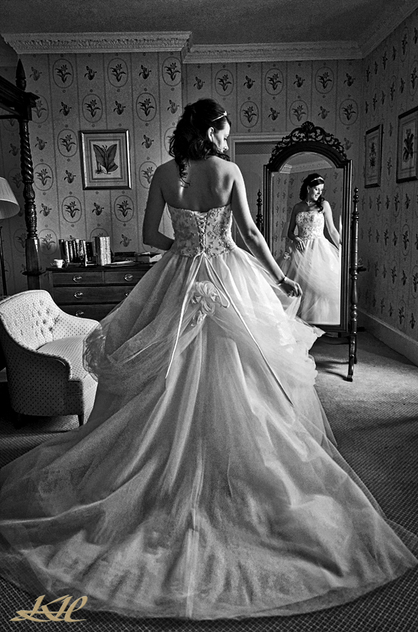 Bride posing by mirror in wedding dress in black & white